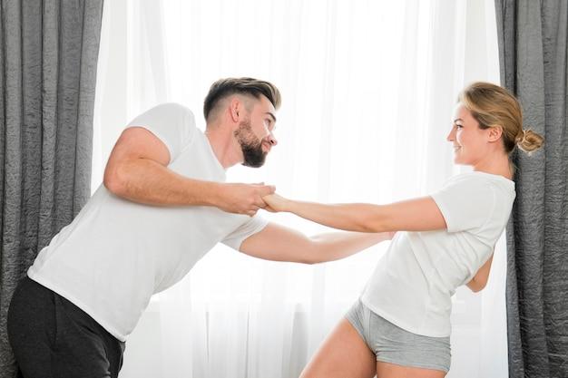 Couple heureux, intérieur, tenant mains