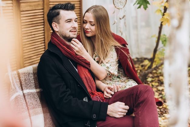 Couple heureux. jeune femme mignonne embrasse son petit ami alors qu'elle était assise sur le banc en automne en plein air. amoureux marchant dans le parc. histoire d'amour et concept de famille