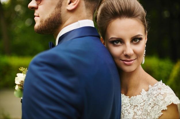 Un couple heureux de jeunes mariés s'embrassant et regardant dans la caméra une belle fille modèle
