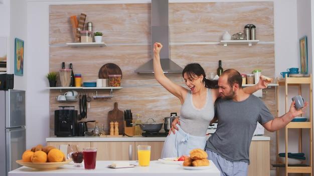 Couple heureux et joyeux sans soucis dansant et chantant dans la cuisine le matin synny. joyeux mari et femme riant, chantant, dansant, écoutant méditer, vivant heureux et sans souci. les gens positifs