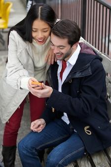 Couple heureux, lecture de sms sur téléphone mobile