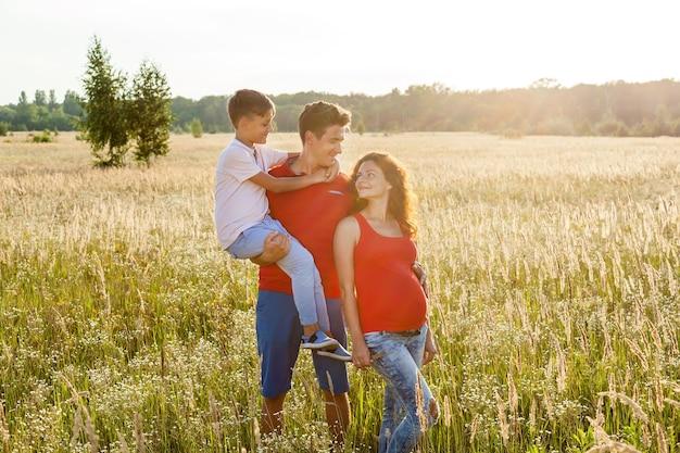 Un couple heureux avec leur fils pose sur le fond d'un champ de blé au coucher du soleil.