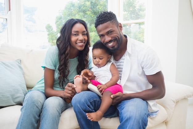 Couple heureux avec leur petite fille sur le canapé