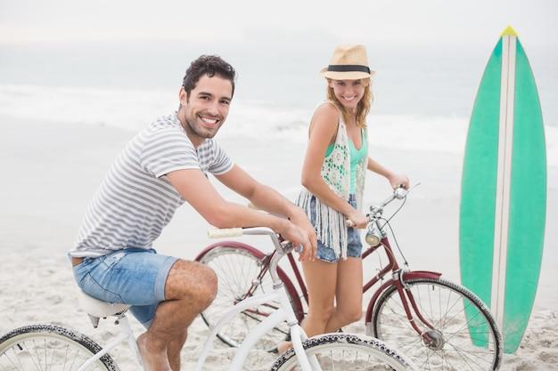 Couple heureux avec leur vélo sur la plage