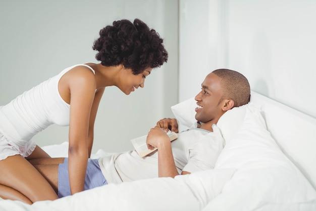 Couple heureux en lisant sur le lit à la maison