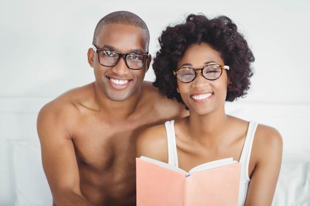 Couple heureux en lisant un livre ensemble sur le lit