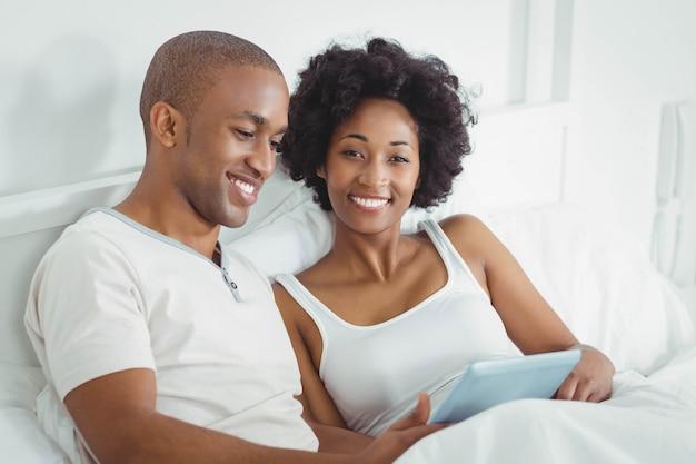 Couple heureux sur le lit avec tablette ensemble