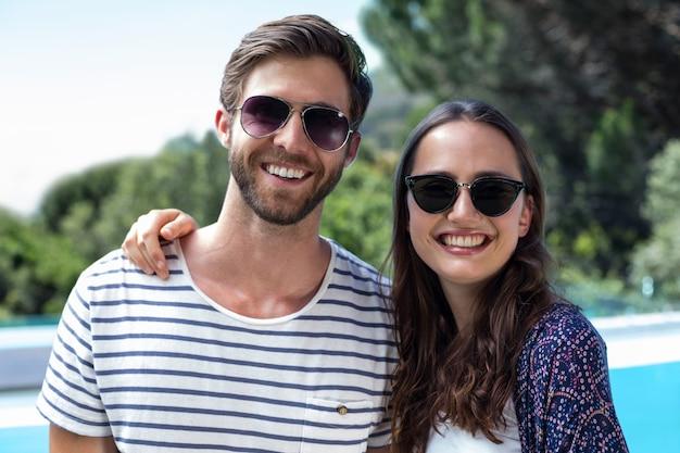 Couple heureux en lunettes de soleil debout près de la piscine