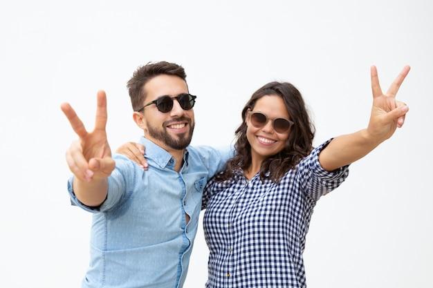 Couple heureux en lunettes de soleil montrant le signe de la victoire