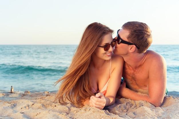 Couple heureux en lunettes de soleil s'amuser sur la plage
