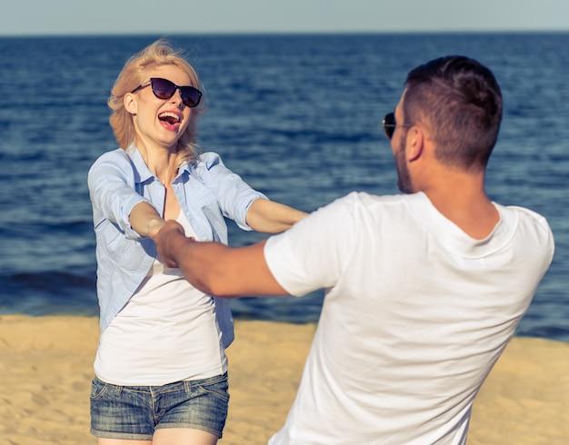 Un couple heureux en lunettes de soleil se tiennent la main.