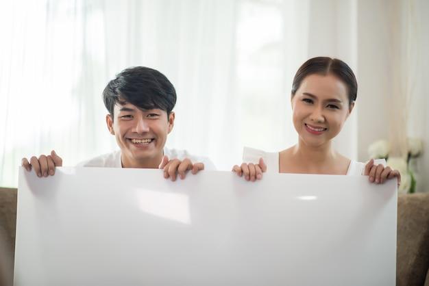 Couple heureux main tenant un espace blanc
