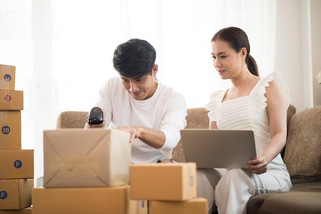Couple heureux à la maison avec les affaires en ligne, marketing en ligne et travail indépendant