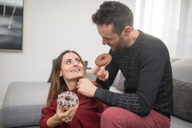 Couple heureux manger des beignets à la maison