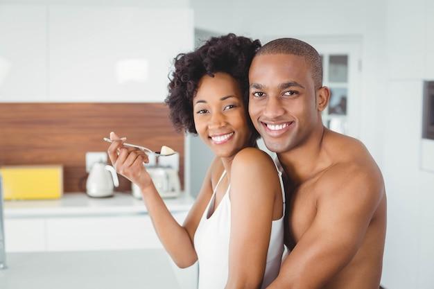 Couple heureux manger des fruits ensemble dans la cuisine à la maison
