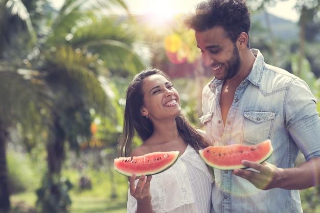 Couple heureux manger un melon d'eau ensemble joyeux