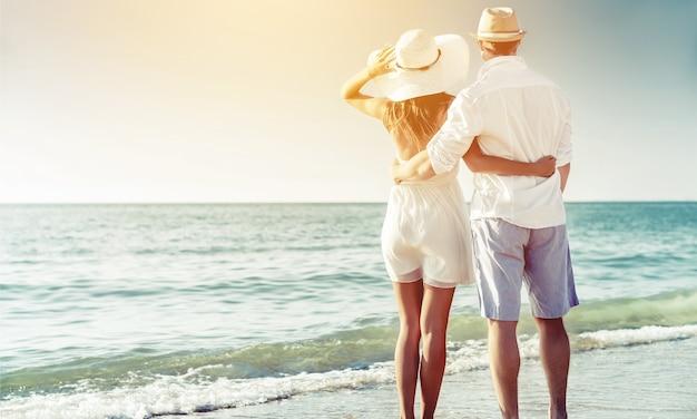 Couple heureux marchant sur la plage au bord de la mer