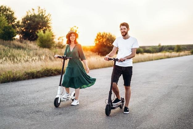 Couple heureux marchant sur des scooters. une jeune femme en robe et chapeau au coucher du soleil