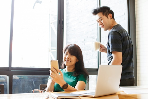 Couple heureux mariage lire un message sms entrant sur un smartphone tout en buvant du café