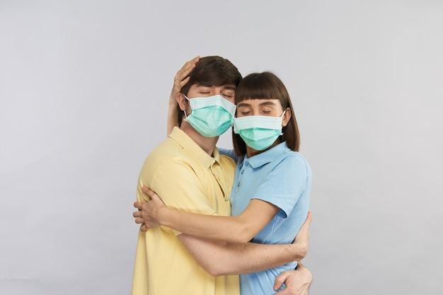 Couple heureux en masques de répétition étreignant les uns les autres isolé sur fond gris