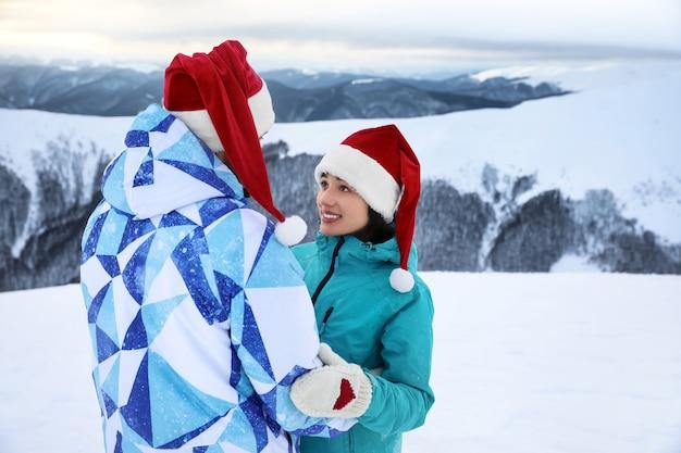 Couple heureux en mitaines chaudes et chapeaux de père noël à la station enneigée. vacances d'hiver