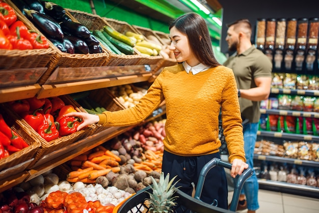 Couple heureux avec panier en épicerie ensemble
