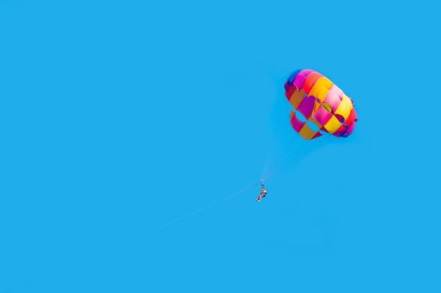 Couple heureux parachute ascensionnel sur la plage tropicale en été couple sous parachute suspendu dans les airs