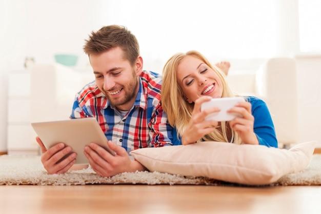 Couple heureux, passer du temps avec des équipements électroniques à la maison