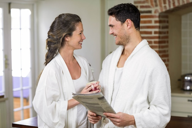 Couple heureux en peignoir lisant un journal dans la cuisine