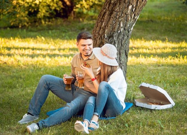 Couple heureux en pique-nique dans le parc. manger de la pizza et boire de la bière