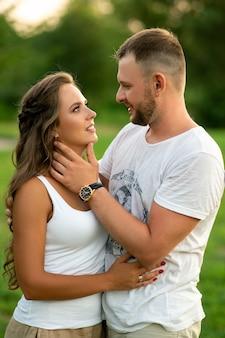 Couple heureux sur un pique-nique souriant les uns aux autres par une journée ensoleillée. concept de personnes, d'amour, de bonheur et de nature