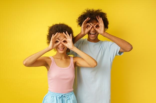 Un couple heureux plaisante en faisant des lunettes avec leurs mains