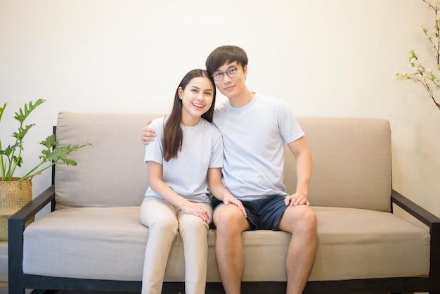 Un couple heureux portant une chemise bleue est assis sur un canapé à la maison