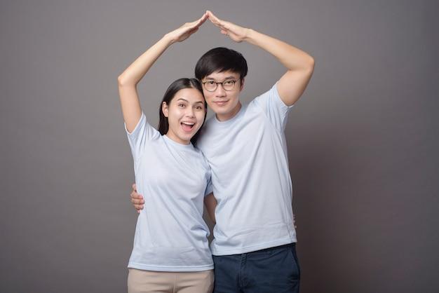 Un couple heureux portant une chemise bleue fait un toit ouvrant en gris