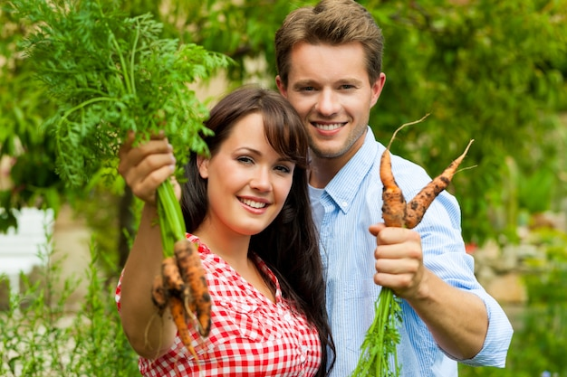 Couple heureux en posant avec les carottes qu'ils viennent de récolter