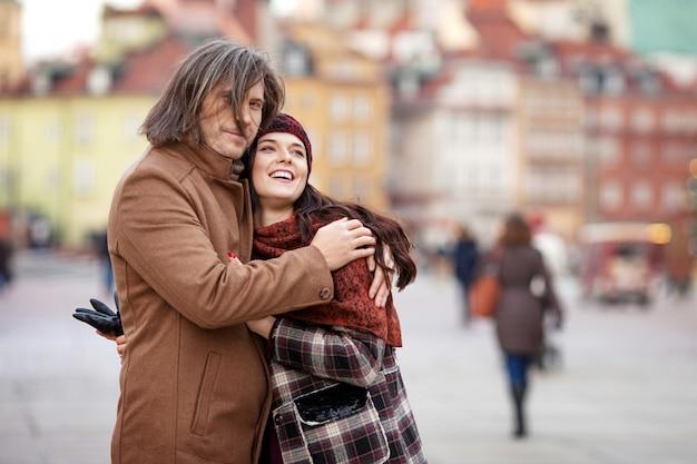 Couple heureux posant sur la vieille place de la ville. très belle femme et son bel homme élégant étreignant dans la rue. heure d'automne ou d'hiver. warsaw, pologne