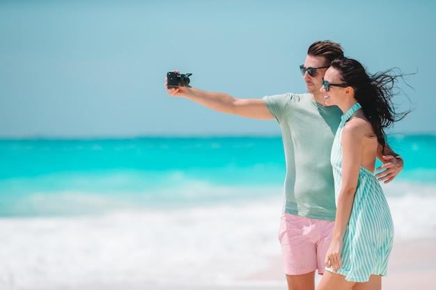 Couple heureux en prenant une photo sur la plage blanche en vacances de lune de miel