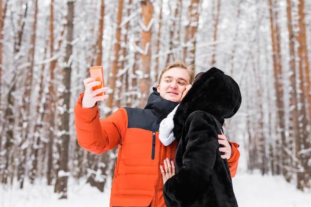 Couple heureux prenant une photo avec un smartphone sur fond d'hiver.
