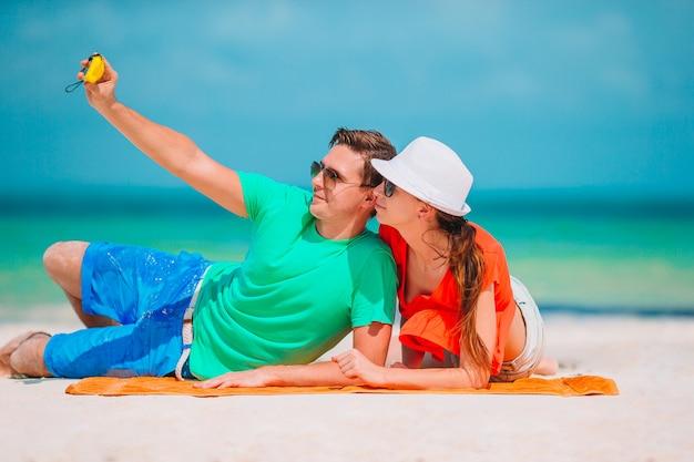 Couple heureux en prenant une photo de soi sur une plage en vacances