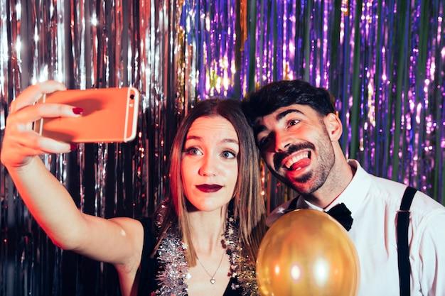 Couple heureux prenant selfie sur la fête du nouvel an