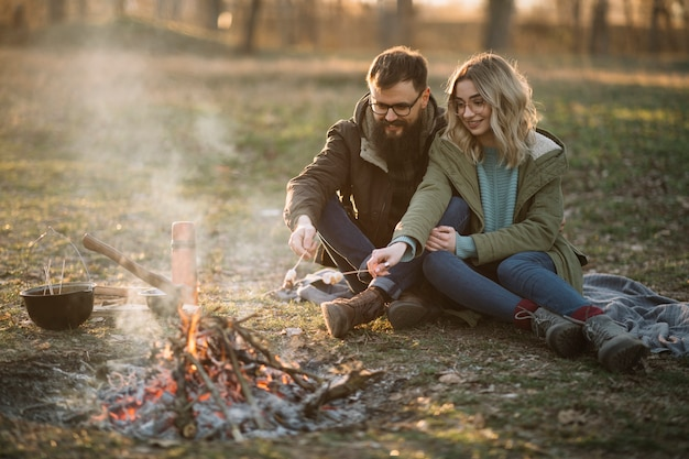 Couple heureux, près, feu camp