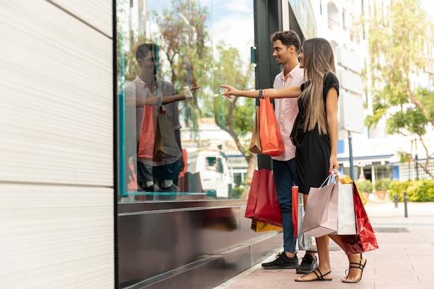 Couple heureux près d'un magasin à la recherche de ventes