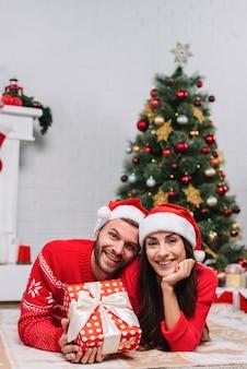 Couple heureux près de sapin de noël