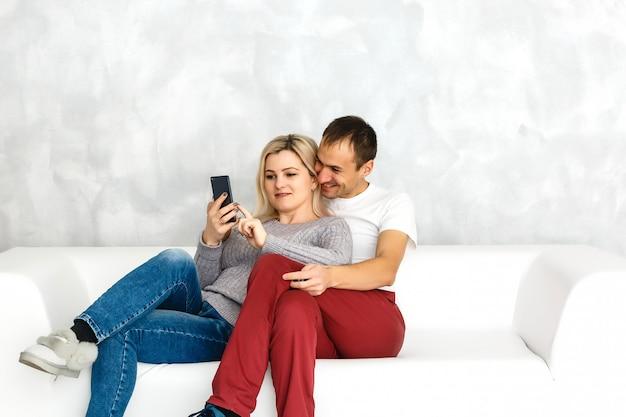 Couple heureux, profitant de contenu multimédia dans un téléphone intelligent, assis sur un canapé à la maison