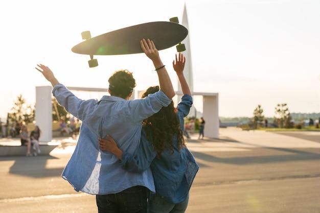 Un couple heureux profite d'une étreinte au coucher du soleil avec les bras levés tient le concept de bonheur et de liberté de longboard