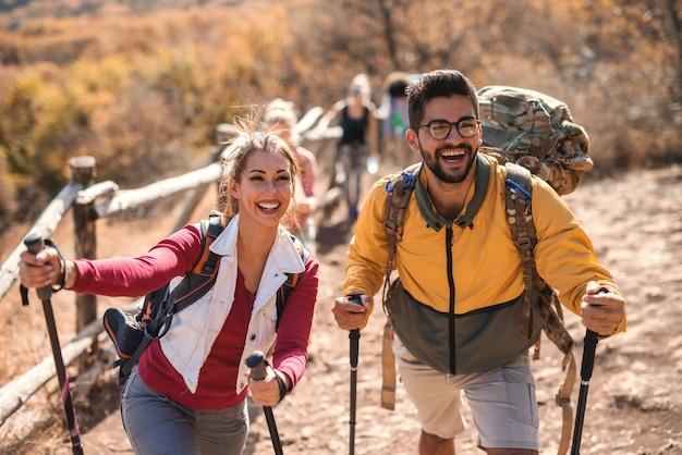Couple heureux en randonnée à l'automne. en arrière-plan reste du groupe.
