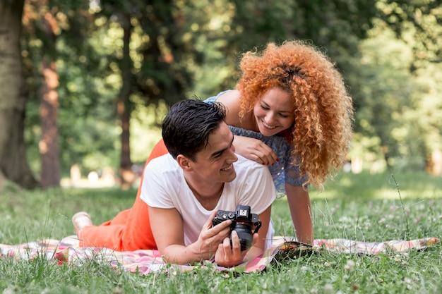 Couple heureux en regardant un appareil photo numérique