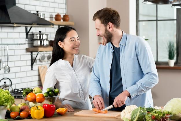 Couple heureux en regardant les uns les autres tout en coupant les carottes sur la planche à découper