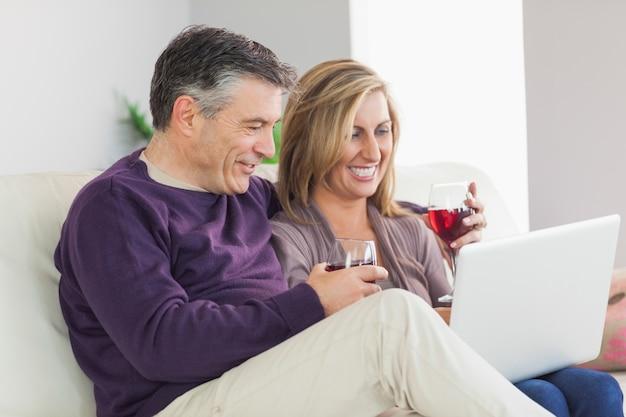 Couple heureux en regardant leur ordinateur portable et boire du vin
