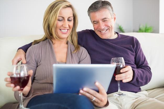 Couple heureux en regardant leur tablette pc et boire du vin